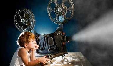 Little boy with a film projector