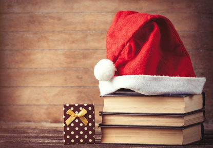 Santas hat over books near gift box on wooden background.