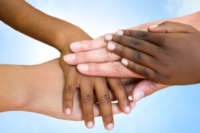 Close up of multiethnic children's hands making pile against blue sky.